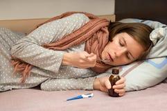 La hembra joven está enferma Ella cogió frío, sintiéndose mal y tomando medicinas fotografía de archivo libre de regalías