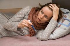La hembra joven está enferma Ella temperatura de medición y mirada del termómetro en horror Alta fiebre imagenes de archivo