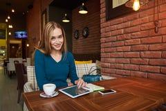 La hembra joven está mirando el vídeo en la tableta digital durante resto en cafetería moderna fotografía de archivo libre de regalías