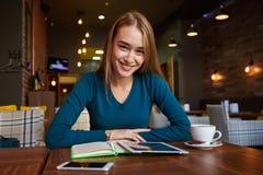 La hembra joven está mirando el vídeo en la tableta digital durante resto en cafetería moderna Foto de archivo libre de regalías