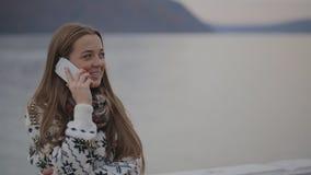 La hembra joven está mirando en la distancia que habla en el teléfono móvil que está fuera de la ciudad, en el aire abierto almacen de video