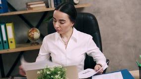 La hembra joven está mirando papeleo su escritorio en oficina