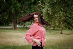 La hembra joven feliz desarrolla el pelo y presenta en cámara Fotos de archivo libres de regalías