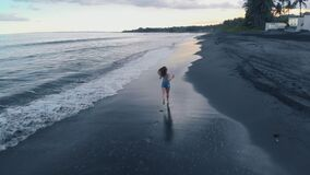 La hembra joven hermosa corre a lo largo de la playa del océano con la arena negra y agita en la puesta del sol en Bali, vídeo 4K almacen de video