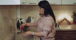 La hembra joven prepara para la cena las legumbres que las lavan en el fregadero en la cocina blanca metrajes