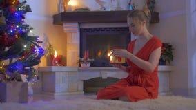 La hembra joven se sienta en la alfombra de hadas y abre su actual árbol de navidad cercano almacen de metraje de vídeo
