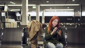 La hembra joven utiliza el teléfono en terminal de aeropuerto