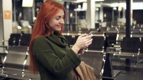 La hembra joven utiliza smartphone en terminal de aeropuerto de la noche