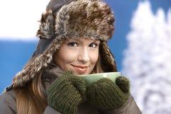 La hembra joven vistió para arriba la sonrisa de consumición caliente del té Fotografía de archivo libre de regalías