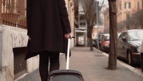 La hembra llega en la nueva ciudad para el viaje de negocios Empresaria con la maleta que camina en la acera, explorando la ciuda almacen de video