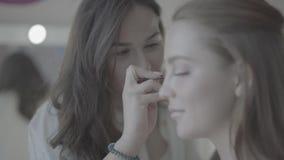 La hembra morena atractiva joven compone al estilista del artista que trabaja cuidadosamente en cara modelo rubia hermosa en el s almacen de video