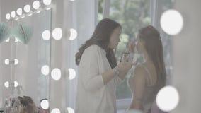 La hembra morena hermosa joven compone al estilista del artista que trabaja cuidadosamente en cara modelo rubia atractiva en el s almacen de metraje de vídeo