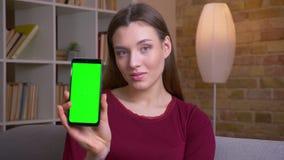 La hembra morena joven y bonita muestra la pantalla verde vertical de la croma del tel?fono que recomienda el app en casa metrajes