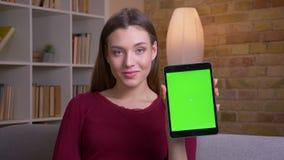 La hembra morena joven y hermosa muestra la pantalla verde vertical de la tableta en la c?mara que recomienda el app en casa metrajes