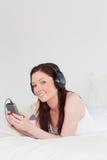 La hembra pelirroja magnífica escucha Foto de archivo