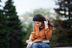 La hembra pensativa reflexiona sobre el libro que ella está leyendo durante su tiempo libre en vacaciones de primavera, mujer jov Fotografía de archivo
