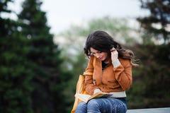La hembra pensativa reflexiona sobre el libro que ella está leyendo durante su tiempo libre en vacaciones de primavera, mujer jov Imágenes de archivo libres de regalías