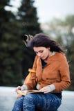La hembra pensativa reflexiona sobre el libro que ella está leyendo durante su tiempo libre en vacaciones de primavera, mujer jov Imagen de archivo