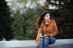 La hembra pensativa reflexiona sobre el libro que ella está leyendo durante su tiempo libre en vacaciones de primavera, mujer jov Imagenes de archivo
