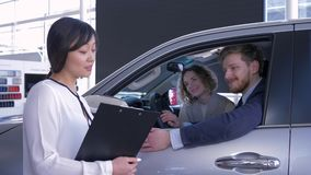La hembra profesional de Asian del encargado informa a la familia joven de los compradores que se sienta en salón del coche mient almacen de video