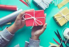 La hembra que adorna la caja de regalo linda presenta en fondo de la mesa de trabajo Fotografía de archivo libre de regalías