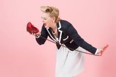 La hembra rubia habla emocionalmente sobre el teléfono Señora que llora en el teléfono rojo de los labios Labios a la conversació foto de archivo libre de regalías