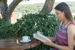 La hembra se sienta cerca por la piscina en el té Canakkale del café de la bebida del libro de lectura del tiempo de verano en Tu Imagen de archivo libre de regalías