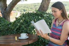 La hembra se sienta cerca por la piscina en el té Canakkale del café de la bebida del libro de lectura del tiempo de verano en Tu Foto de archivo