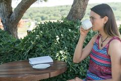 La hembra se sienta cerca por la piscina en el té Canakkale del café de la bebida del tiempo de verano en Turquía 2017 Fotografía de archivo