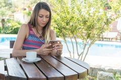 La hembra se sienta cerca por la piscina en el tiempo de verano DPlaying con el té Canakkale del café de la bebida del teléfono m Imágenes de archivo libres de regalías