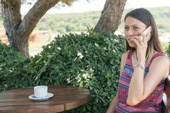 La hembra se sienta cerca por la piscina en el tiempo de verano que habla en el té Canakkale del café de la bebida del teléfono e Foto de archivo libre de regalías