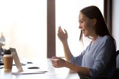 La hembra sorprendente del empleado que mira el canto del ordenador cree en suerte imágenes de archivo libres de regalías