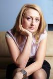 La hembra triste e infeliz se sienta en el sofá Foto de archivo libre de regalías