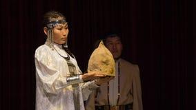La hembra yakuta da un tocado festivo al hombre Imagenes de archivo
