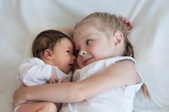 La hermana abraza a su hermano menor Foto de archivo