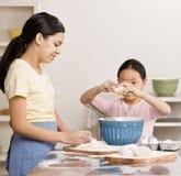 La hermana amasa la pasta mientras que otras grietas eggs imagen de archivo