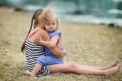 La hermana del espantapájaros abraza cariñosamente a su hermana con Síndrome de Down Imagen de archivo