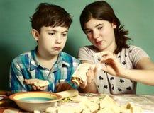 La hermana enseña muchacho del hermano a cómo cocer las empanadas de manzana Imagen de archivo