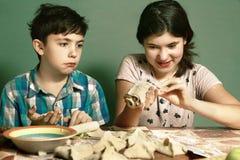 La hermana enseña muchacho del hermano a cómo cocer las empanadas de manzana Imagen de archivo libre de regalías