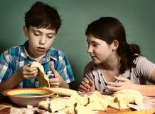 La hermana enseña muchacho del hermano a cómo cocer las empanadas de manzana Fotografía de archivo libre de regalías