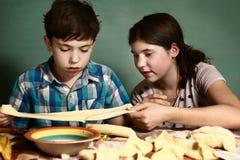 La hermana enseña muchacho del hermano a cómo cocer las empanadas de manzana Fotografía de archivo