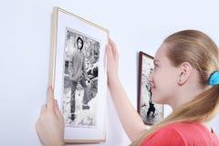 La hermana mira al hermano de la foto en la pared blanca Fotos de archivo