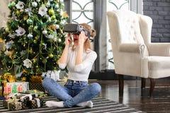 La hermana que prueba los vidrios de la realidad virtual acerca al árbol del Año Nuevo Foto de archivo libre de regalías