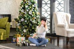 La hermana que prueba los vidrios de la realidad virtual acerca al árbol del Año Nuevo Imagen de archivo