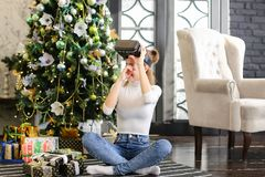 La hermana que prueba los vidrios de la realidad virtual acerca al árbol del Año Nuevo Imágenes de archivo libres de regalías