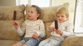 La hermana y el hermano comen el helado en los palillos que se sientan en el sofá Tiro del PDA almacen de metraje de vídeo