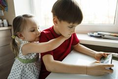 La hermana y el hermano se están sentando en la cocina y están jugando con el teléfono foto de archivo libre de regalías