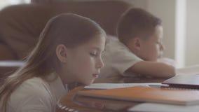 La hermana y el hermano se sientan en la tabla y preparación de la fabricación de la escuela La muchacha se cae dormido en la tab almacen de metraje de vídeo
