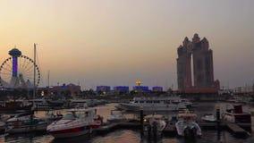 La hermosa vista de Marina Mall y el puerto deportivo observan la rueda en la puesta del sol - playa y los barcos de Abu Dhabi metrajes