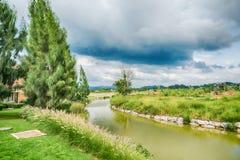 La hermosa vista de un pequeño lago afiló por los árboles verdes Imagenes de archivo